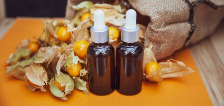 Bottles with physalis oil  and fresh  fruit  on orange  background Imagens