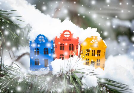 Toy houses  on a natural natural background of a real fir in the snow. Concept of winter, Christmas, new year,  warm, cozy in the city.
