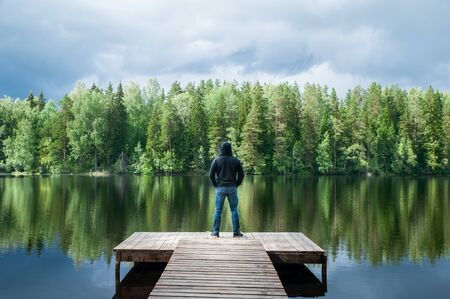 Man stands on the pier of a beautiful lake, panoramic photo. The concept of freedom and independence, a symbolic photo of the beauty of nature