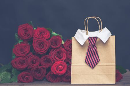 Concept of a gift for the day of lovers from a man.  large armful of red roses and a gift bag with a mens tie.
