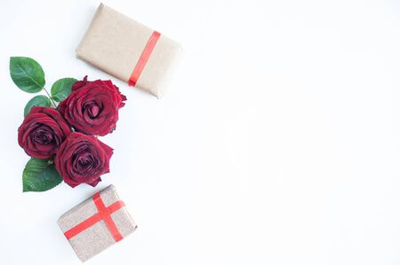 Flat Lay Background, flower pattern, Valentines Day, the theme of lovers. Red roses and gifts with ribbons on a white background, isolated