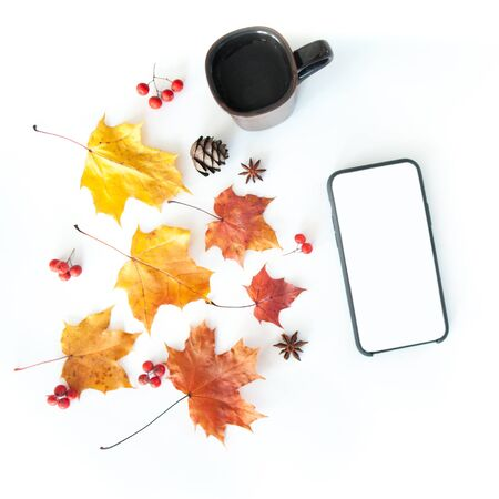 Autumn composition with a phone, a glass and autumn leaves on a white background, flat lay Imagens