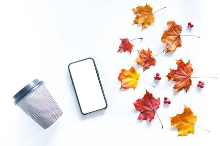 Autumn composition with a phone, a paper glass and autumn leaves on a white background, flat lay