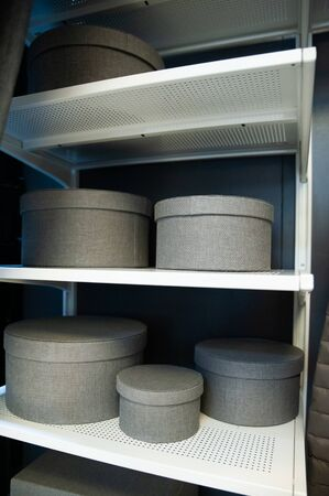 Round boxes for storage of gray color on the shelf, the theme of storage, cleaning in the house
