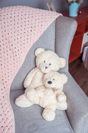 Two white toy teddy bears on a chair and a soft pink plaid