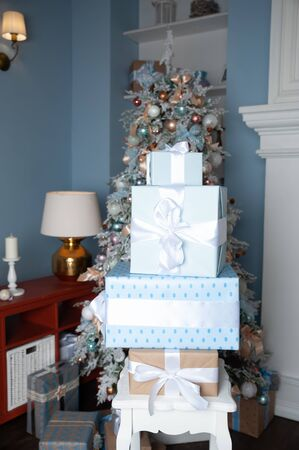 Boxes tied with ribbons one on one against the background of a Christmas tree in gentle blue tones. Symbol of congratulations and gifts for the New Year and Christmas. Stok Fotoğraf