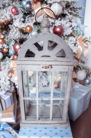 Vintage wooden chest for candles on the background of a decorated white New Year tree, New Year mood, delicate pastel colors