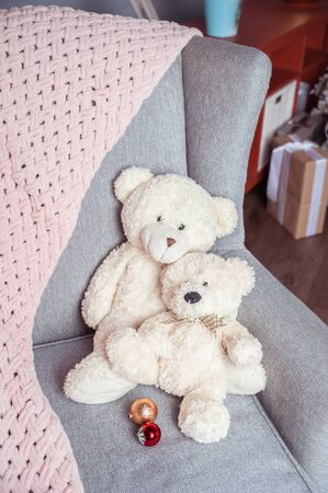Two white toy teddy bears on a chair and a soft pink plaid, New Years mood Stok Fotoğraf
