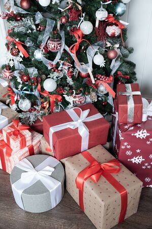 Boxes tied with ribbons under a Christmas tree in red colors. Symbol of congratulations and gifts for the New Year and Christmas.