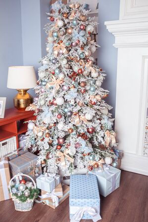 White decorated Christmas tree with many gifts underneath in gentle pastel colors. Good New Year spirit