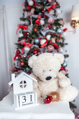 Wooden calendar  and toy bear  on the background of a Christmas tree with a date of December 31, a symbol of the new year Stok Fotoğraf