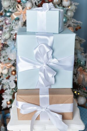 Boxes tied with ribbons one on one against the background of a Christmas tree in gentle blue tones. Symbol of congratulations and gifts for the New Year and Christmas. Stock Photo