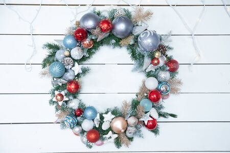 Decorated Christmas wreath on a white wall, New Year mood