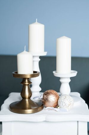 Three Stylish white large candles on the table, and New Years balls, photos in gentle pastel colors. Christmas mood 版權商用圖片