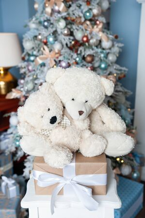 Christmas mood, Two white toy teddy bears  against the background of a white decorated Christmas tree. Waiting for a miracle, New Year decorations Stok Fotoğraf