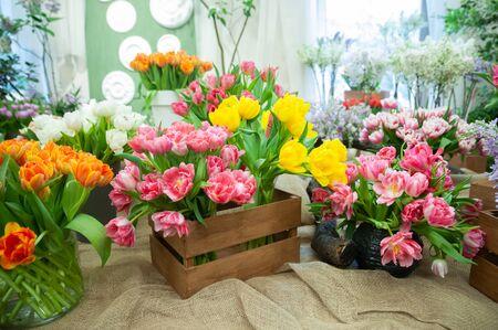 Blumenladen, Verkauf von Blumen. Schöne blühende Komposition aus bunten Tulpen, heller bunter Tulpenfotohintergrund,