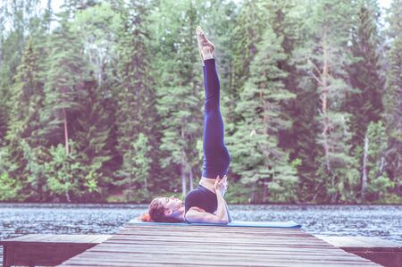 Young yogi  girl  practicing yoga, standing in Salamba Sarvangasana exercise, supported Shoulder stand pose on the lake.  Concept of healthy life and natural balance