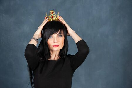Very beautiful girl with with a very nice face and a smile trying on the crown. Concept queen, a princess, a gorgeous woman. Studio portrait on a monochrome blue, trendy shabby background. Space for text
