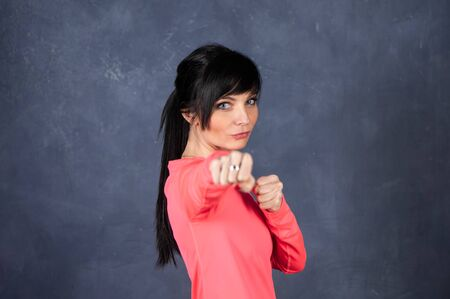 Trendy beautiful girl, brunette in bright sports clothes  looks into the camera, combat training. The concept of sports, fitness, space for text