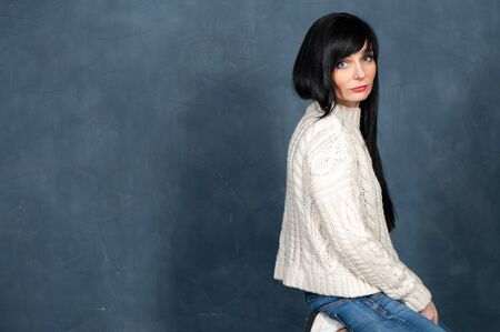 Beautiful girl with long, black hair in a white knitted sweater and jeans is on her knees and sadly looks into the camera, a space for text. Studio portrait on a monochrome blue, trendy shabby background Banque d'images