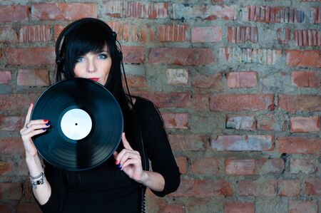 Trendy beautiful girl brunette DJ with a vinyl record in her hands, looking into the camera, against a background of a brick wall, space for text. Theme of music Banque d'images - 146615069