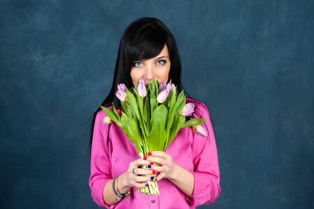 Fashionable beautiful girl, brunette in a bright pink shirt, with a bouquet of tulips flowers, looking at the camera, the theme of summer, spring. Banque d'images - 146615070