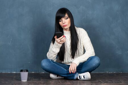 Trendy brunette girl sits on the floor, looking at the smartphone screen, upset. Studio portrait on a monochrome blue, trendy shabby background,  space for text. Banque d'images