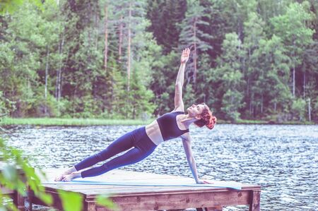 Young yogi girl practicing yoga, Side Plank exercise, Vasisthasana pose on the lake. The concept of appeasement, healthy lifestyle. Banque d'images - 147651335