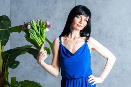 Expressive and glamorous beautiful  girl in a blue dress with a bouquet of tulips in hand . Trendy  fashion  summer  and spring concept. Banque d'images - 147065945