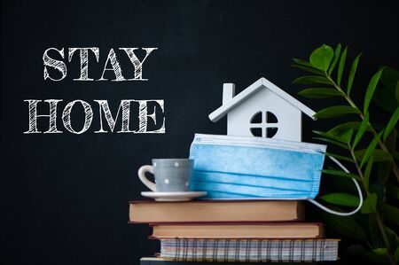 Stay home concept of selfisolation during the Covid-19 coronavirus pandemic. Cute home interior, house, books, flowers and the inscription - Stay home Banque d'images - 147067159