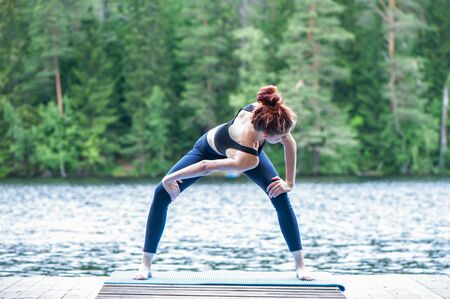Young yogi  girl  practicing yoga, twisting in variation of Goddess on the pier of a beautiful lake.   Concept of healthy life and natural balance