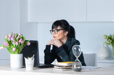 Beautiful girl, brunette in a suit and glasses, looking at the laptop, thinking about the tasks at work. Banque d'images - 150400752