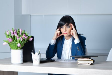 Businesswoman brunette in a suit at her desk think about solving the problem. Office work concept Banque d'images - 150400756