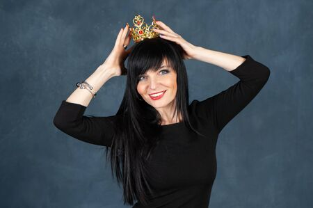 Very beautiful girl with with a very nice face and a smile trying on the crown. Concept queen, a princess, a gorgeous woman. Studio portrait on a monochrome blue, trendy shabby background Banque d'images