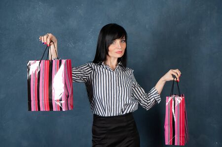 Fashionablepretty girl, brunette  with shopping bag, she smiles. Studio portrait of a woman on monochrome blue, trendy shabby background, shopping theme