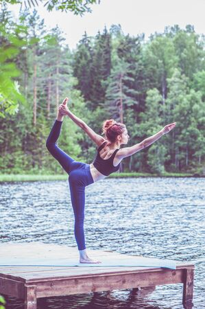 Young yogi  girl  practicing yoga, variation of Natarajasana, Lord of the Dance Pose on the lake.  Concept of healthy life and natural balance