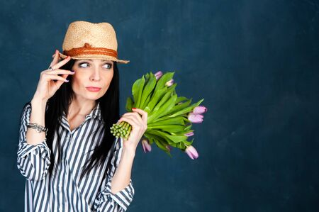 Fashionable beautiful girl, brunette in a summer straw hat and striped shirt, with a bouquet of tulips flowers, space for text, the theme of summer, spring.