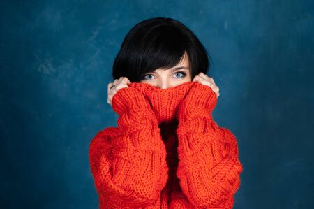 Beautiful girl, brunette in a bright orange sweater, warming up, she's cold. The theme of autumn and coolness. Studio portrait of a woman on a monochrome blue, trendy shabby background