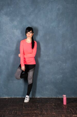 Modern beautiful girl, brunette in bright sports clothes stands by the wall and looks into the camera, ready to start training. Concept sports, fitness