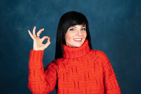 Trendy beautiful girl, brunette in a bright orange sweater, shows an ok sign and smiling . The theme of autumn and coolness. Studio portrait of a woman on a monochrome blue, trendy shabby background Banque d'images