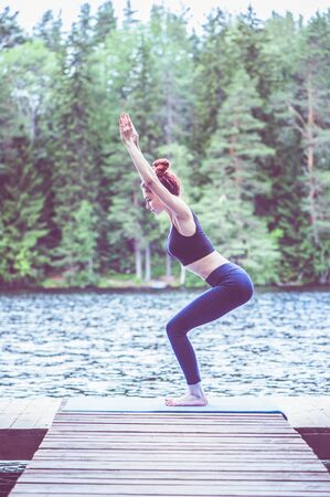Young yogi  girl  practicing yoga, standing in Utkatasana exercise, Chair pose on the lake.  Concept of healthy life and natural balance