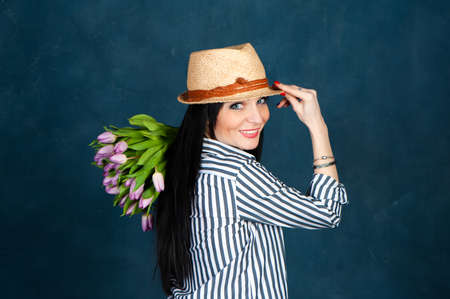 Fashionable beautiful girl, brunette in a summer straw hat and striped shirt, with a bouquet of tulips flowers, looks at the camera, the theme of summer, spring.