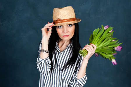 Trendy beautiful girl, brunette in a summer straw hat and striped shirt, with a bouquet of tulips flowers, looks at the camera, the theme of summer, spring. Banque d'images