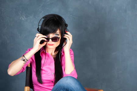 Trendy beautiful girl brunette DJ in headphones, listens to and records music, studio portrait on a monochrome blue, trendy shabby background, space for text. Theme of music Banque d'images