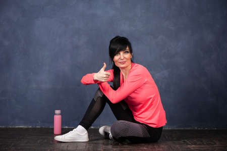 Trendy beautiful girl, brunette in bright sports clothes sits on the floor and looks into the camera, thumbs up. Ready to start training. The concept of sports, fitness, space for text