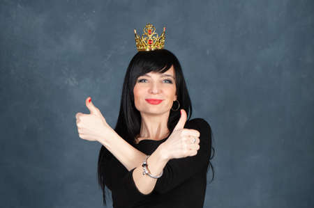 Expressive and glamorous beautiful girl, brunette in a black dress and the crown, showing his fingers up as a symbol of luck and success. Beautiful and slender woman looks at the camera, smiles, studio portrait on a monochrome blue, trendy shabby background