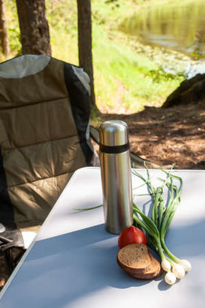 Theme of hiking, tourism and picnic a symbolic image, thermos and food on the table