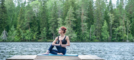 Young attractive girl doing Half lord of the fishes exercise, Ardha Matsyendrasana pose with namaste on the lake. The concept of appeasement, healthy lifestyle. Panoramic view Banque d'images