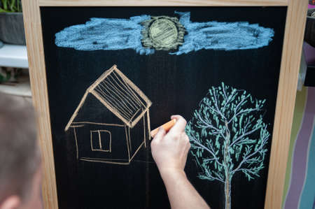Hand is drawing children's drawing, a house and a tree, the concept of creativity with colored chalk on a blackboard.