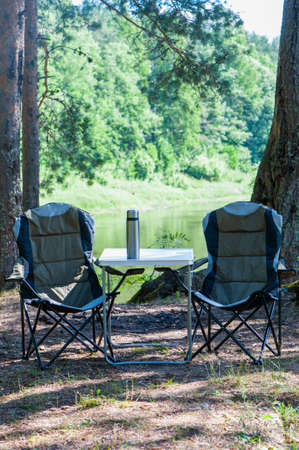 Theme of hiking and tourism, a symbolic landscape, two empty camping chairs and picnic table are on the beautiful beach, summer sunny day